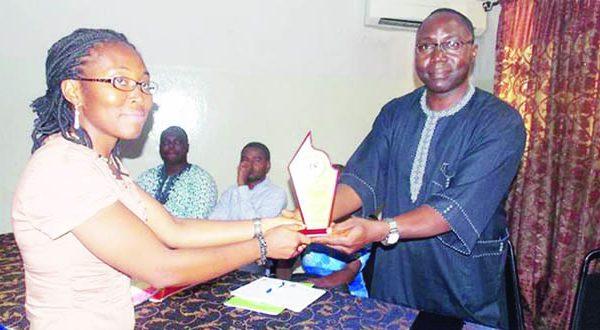 Jennifer-Ehidiamen-recieving-her-award-from-Fola-Adekeye